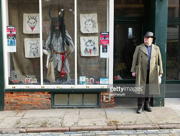 A man stands next to a window display showing the folklore figure Krampus ahead of a charity event on December 3 2016 in Whitby United Kingdom The...