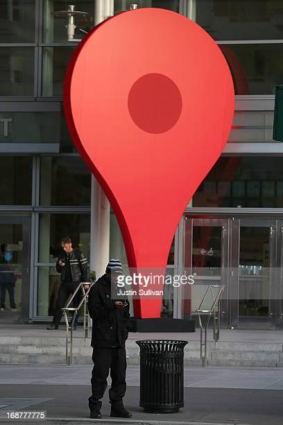 A man stands next to an oversized Google map marker pin as attendees wait to enter the Google I/O developers conference at the Moscone Center on May...