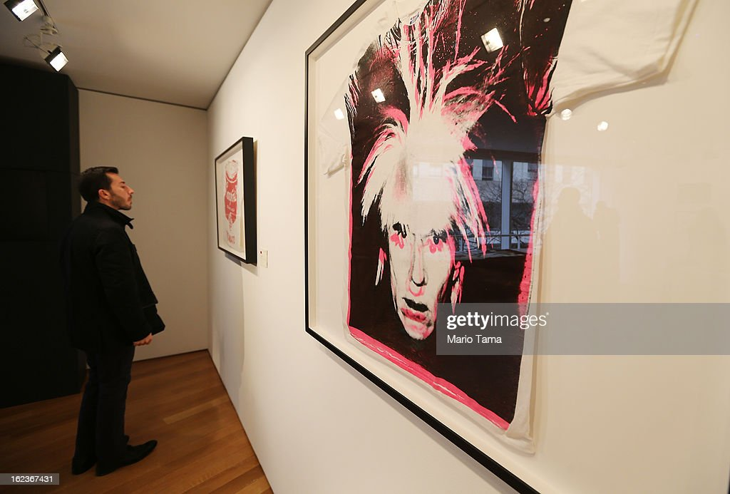 A man stands next to Andy Warhol's 'Self-Portrait with Fright Wig' (R) at a press preview for the Andy Warhol @ Christie's online-only sale on February 22, 2013 in New York City. The sale will be the first ever online-only sale of Warhol's work with 125 pieces and runs February 26 to March 5.