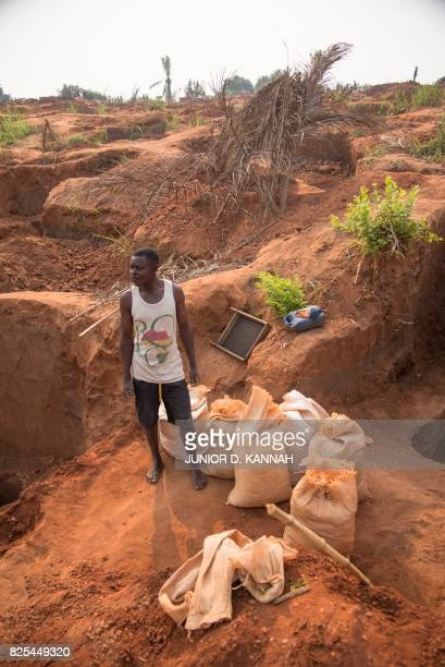 A man stands next to bags of gravel at the Nkanzala abandoned mine in Tshikapa in Democratic Republic of Congo's central Kasai region on July 29 2017...
