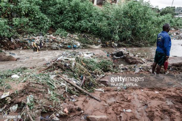 Man stands next to debris after torrential rains and flash floods destroyed houses at an informal settlement of BottleBrush, south of Durban, on...