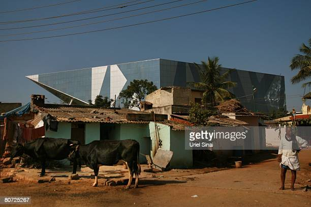 A man stands next to his home as one of the Electronic city buildings is seen in the back on April 13 2008 in Bangalore India Many residents work for...