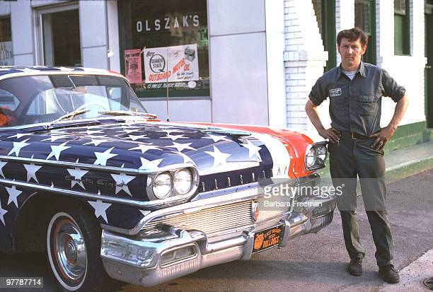 A man stands next to his Oldsmobile 88 patriotically painted with stars and stripes decorations in celebration of the United States' bicentennial...