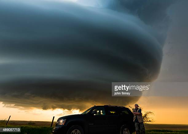 CONTENT] Man stands next to his SUV car with an impressive looking mother ship shaped super cell cloud behind him Taken at sunset Tornado alley