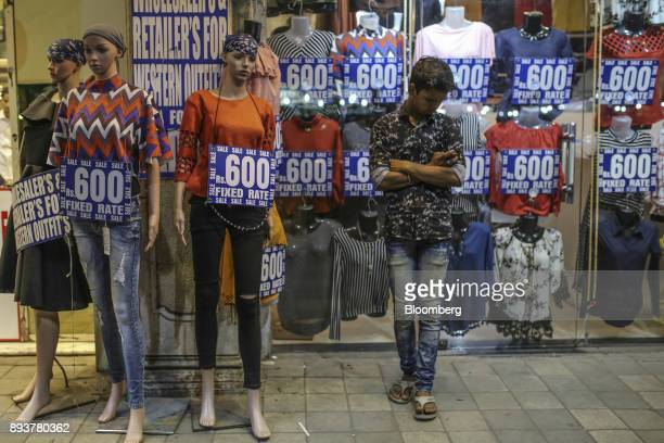 A man stands next to mannequins outside a clothing store in Mumbai India on Friday Dec 15 2017 India's inflation surged past the central bank's...