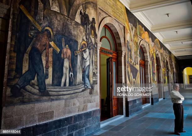 A man stands next to murals by Mexican artist Diego Rivera in the Education Secretariat in Mexico City on April 2017 Rivera was the most visible...
