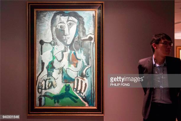A man stands next to Pablo Picasso's 'Femme au chat assise dans un fauteuil' during a media preview of Christie's Hong Kong Spring Sales in Hong Kong...
