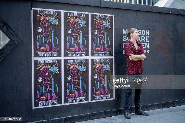 Man stands next to posters for the Foo Fighters show outside as Madison Square Garden reopens with the first full capacity concert since March 2020...