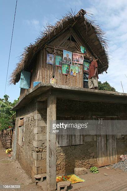 A man stands next to presidential campaign posters on November 2 2010 in the Comoros Island of Moheli The governors of the archipelago's three...