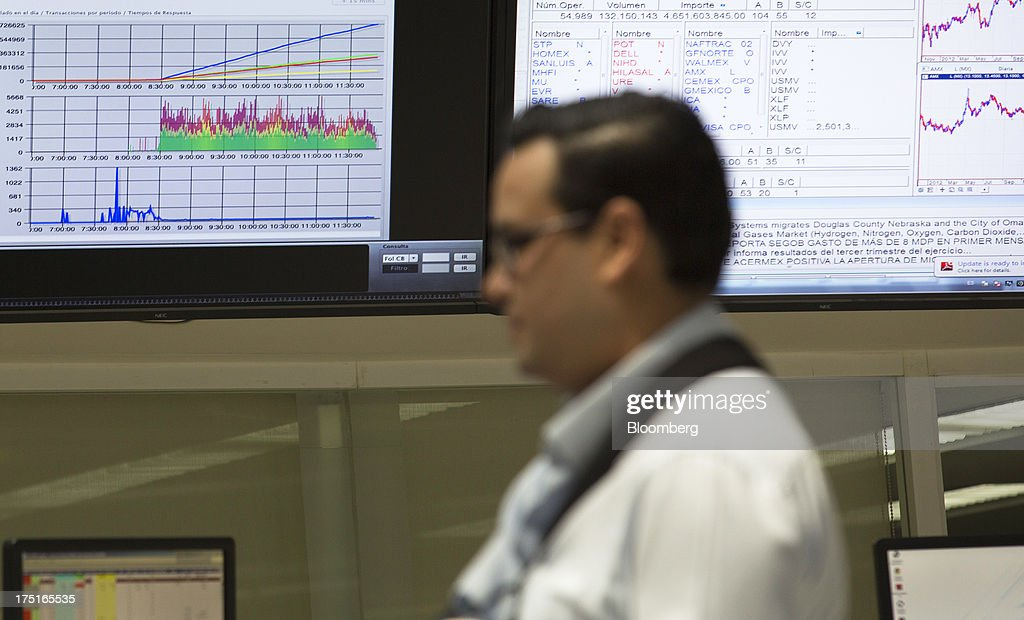 A man stands next to screens in the trading gallery of Bolsa Mexicana de Valores (BMV), Mexico's stock exchange, in Mexico City, Mexico, on Wednesday, July 31, 2013. Mexico's economy is forecast to grow 2.8 percent this year based on analyst estimates compiled by Bloomberg. Photographer: Susana Gonzalez/Bloomberg via Getty Images