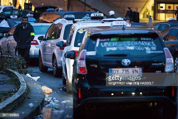 A man stands next to taxicabs lined up during a protest at Porte Maillot in Paris against private hire services on January 28 2016 Taxi drivers are...