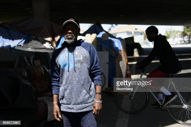 A man stands next to tents under an overpass at the 27th and Northgate homeless encampment in Oakland California US on Friday May 11 2018 The city of...