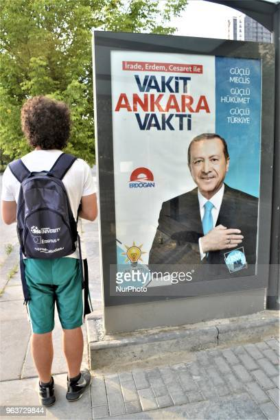 A man stands next to the ruling Justice and Development Party's billboard picturing President Recep Tayyip Erdogan for the early presidential and...