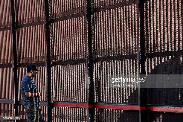 A man stands next to the US Mexico border wall on November 19 2014 in Calexico California US President Barack Obama plans to announce executive...