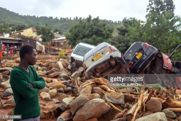 A man stands next to the wreckage a vehicles washed away on March 18 2019 in Chimanimani eastern Zimbabwe after the area was hit by the cyclone Idai...