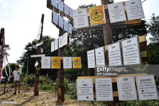 A man stands next to totems with signs reading 'Airport no' and descriptions of events relating to the airport project in a timeline during a twoday...