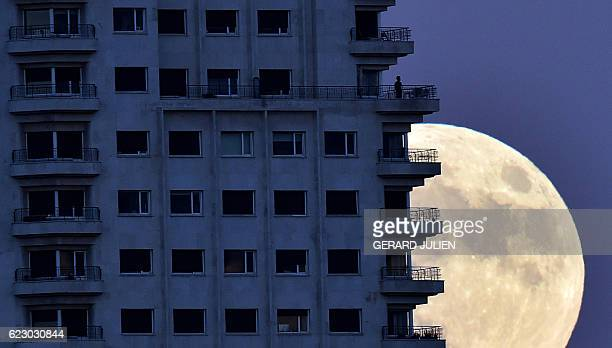 A man stands on a balcony of a building of Madrid as the moon rises in background on November 13 on the eve of a 'supermoon' On November 14 the moon...