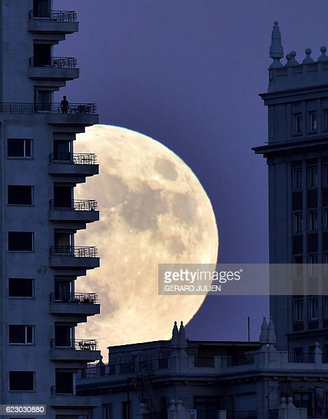 TOPSHOT A man stands on a balcony of a building of Madrid as the moon rises in background on November 13 on the eve of a 'supermoon' On November 14...