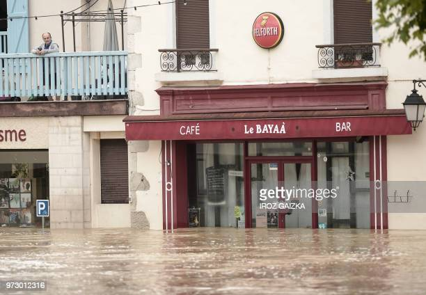 A man stands on a balcony watching flood waters sweep through the streets following heavy rains in SaliesdeBearn south western France on June 13 2018