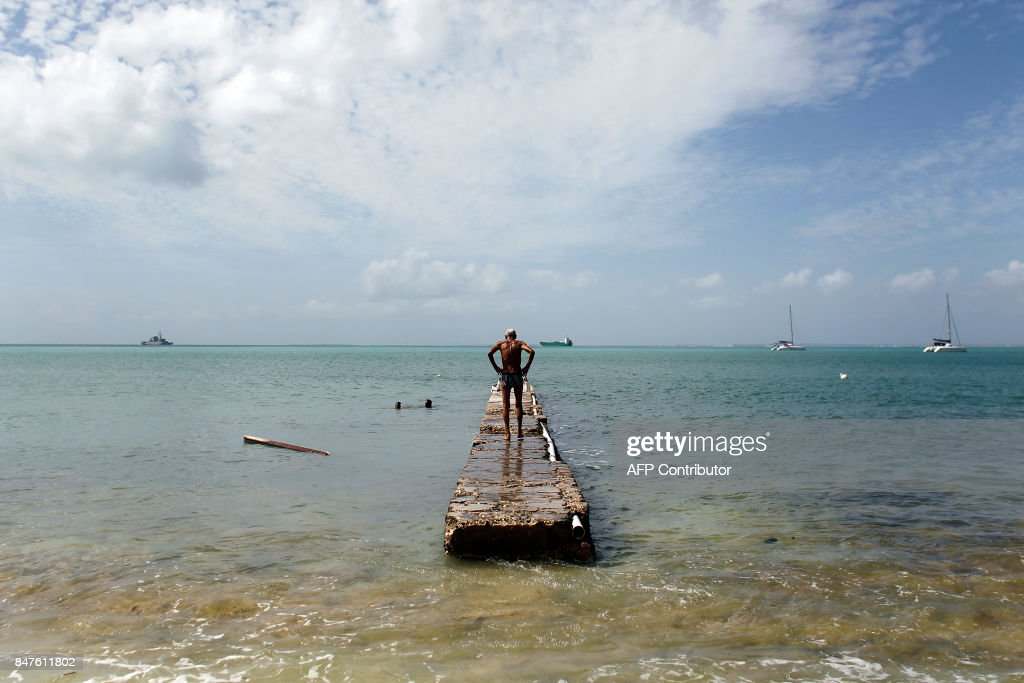 TOPSHOT - A man stands on a damage pier days after this Caribbean island sustained extensive damage in the wake of Hurricane Irma, Friday, September 15, 2017 in St. Martin. / AFP PHOTO / Ricardo ARDUENGO