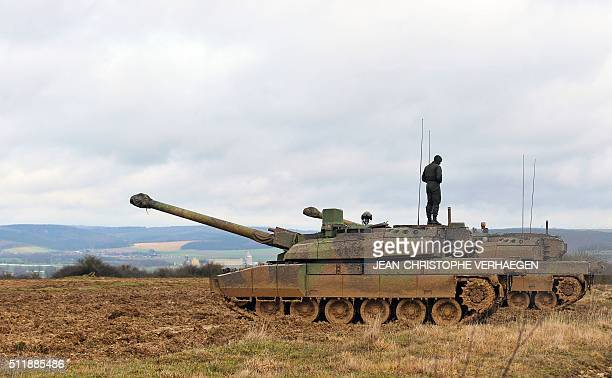 Man stands on a French-made Leclerc tank during a demonstration at the 1st Hunter Regiment, in Thierville-sur-Meuse, eastern France on February 23,...