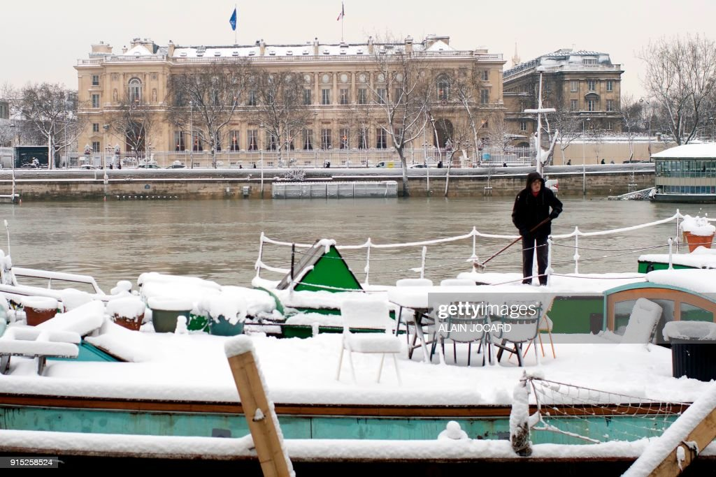 A Man Stands On A Houseboat Moored On The Banks Of The Seine River
