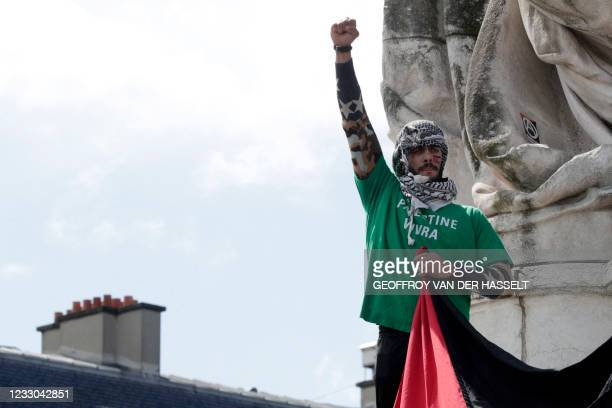 """Man stands on a pedestal wearing a shirt reading """"Palestine will live"""" as protesters shout slogans and wave Palestinian flags during a demonstration..."""