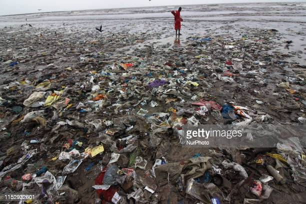 A man stands on a plastic waste at a beach in Mumbai India on 30 June 2019 The trash was pushed onto Juhu beach by a recent storm