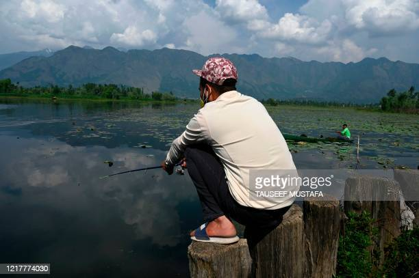 Man stands on a pole while fishing on the polluted Nigeen lake on the 'World Environment Day' in Srinagar on June 5, 2020.