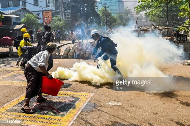 Man stands on a poster featuring armed forces chief Senior General Min Aung Hlaing as he attempts to douse tear gas during a crackdown by security...