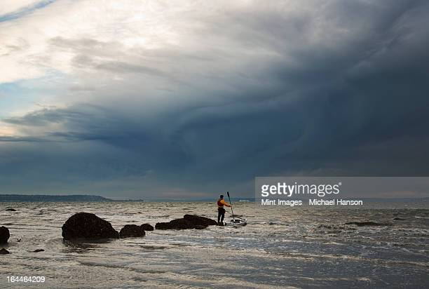 a man stands on a rock in the middle of the puget sound with his sea kayak floating next to him. - sea kayaking stock pictures, royalty-free photos & images