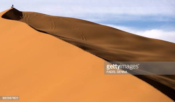TOPSHOT A man stands on a sand dune during the Gallops of Morocco equestrian race in the desert of Merzouga in the southern Moroccan Sahara desert on...