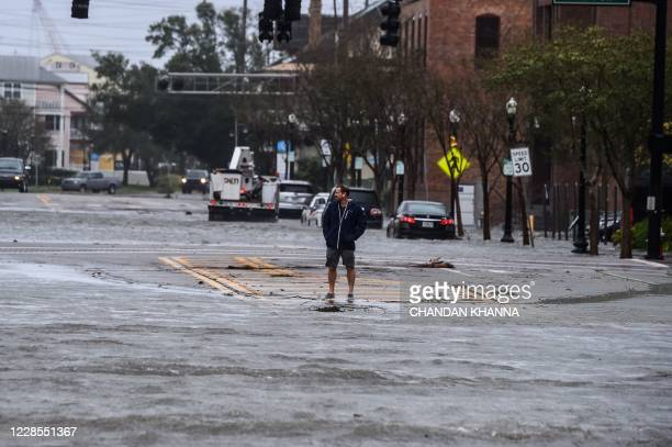 TOPSHOT A man stands on a street flooded by Hurricane Sally in Pensacola Florida on September 16 2020 Hurricane Sally barrelled into the US Gulf...