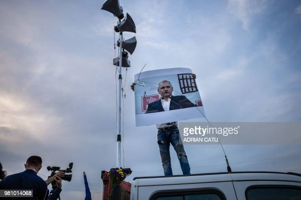 TOPSHOT A man stands on a truck holding a portrait of Liviu Dragnea leader of the ruling leftwing social democrat party and president of the Deputy...