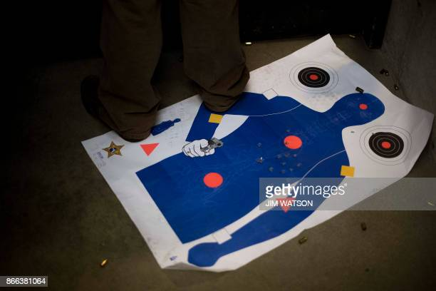 A man stands on a used target as he shoots at the Lynchburg Arms Indoor Shooting Range in Lynchburg Virginia on October 20 2017 Virginia residents go...