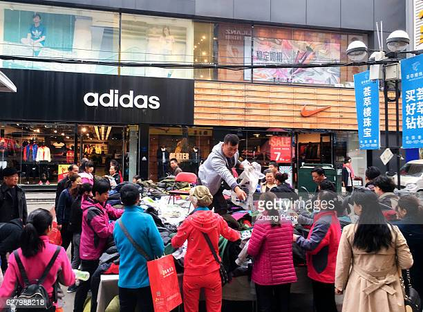 Man stands on a vendor cart and sells discount clothes to pedestrians on a business street While China has one of the most rapidly growing economies...