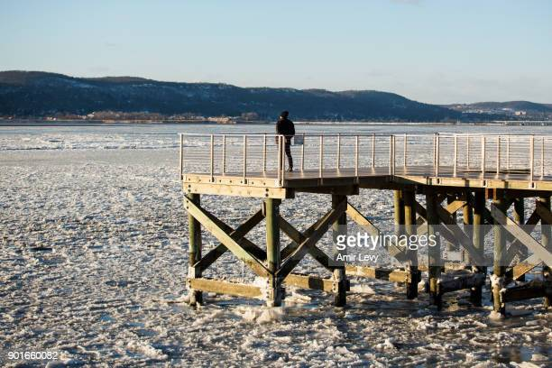 A man stands on a waterfront deck near the frozen Hudson River on January 5 2018 in Dobbs Ferry New York Extreme low tempratures and wind are...