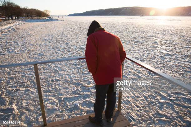 A man stands on a watrfront deck near the frozen Hudson River on January 5 2018 in Dobbs Ferry New YorkExtreme low tempratures and wind are expected...