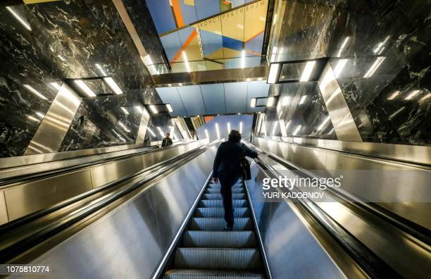 A man stands on an escalator going up at Khoroshevskaya metro station in Moscow on November 10 2018 Moscow's metro system is famed for its Stalinera...