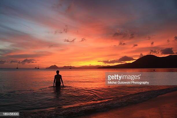 man stands on beach during sunset, martinique - martinique stock photos and pictures