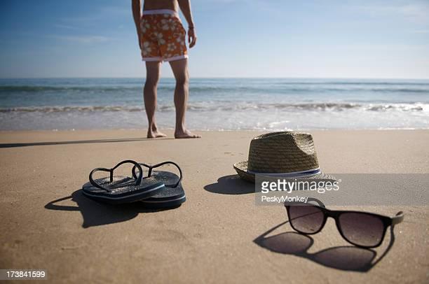 Hombre s'encuentra en la playa sombrero y gafas de sol Flipflops pantalón corto de Surf