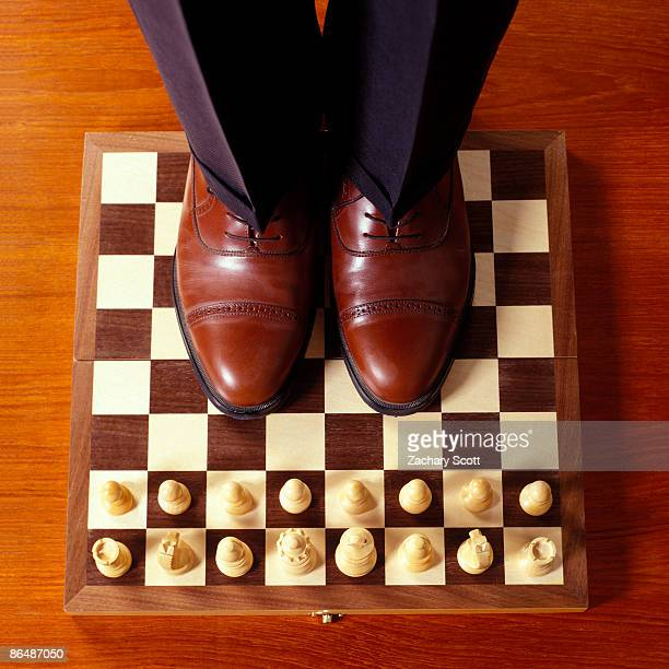 man stands on chess board facing opponent