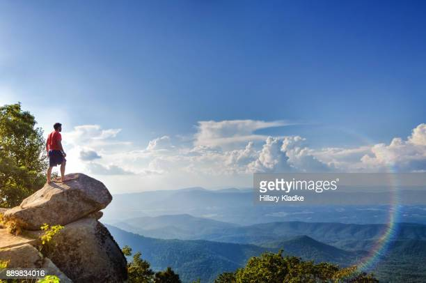 man stands on edge of mountain overlooking blue ridge mountains - viewpoint stock photos and pictures