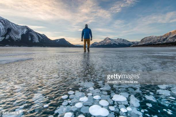 Man stands on frozen lake surface, looks towards mountains
