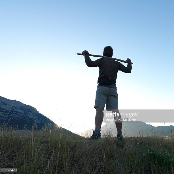 Man stands on grassy hill, watches sunrise