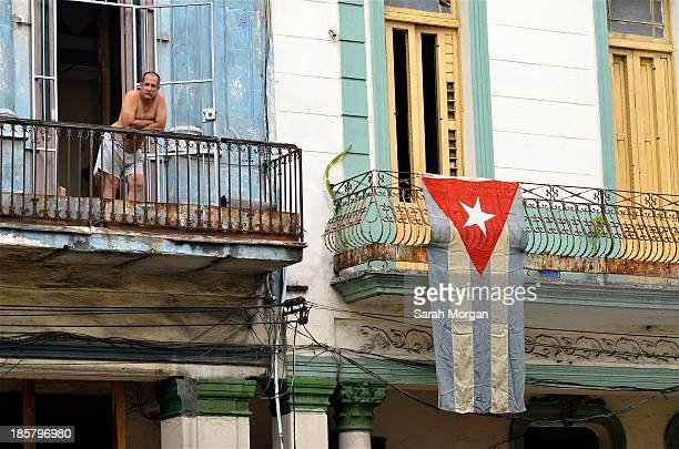 Man stands on his balcony in Havana, Cuba. A large Cuban flag hangs from the balcony next to him. It is a time of economic and political change for...