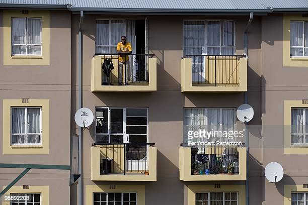 A man stands on his balcony of a newly constructed security complex on January 15 in the Kliptown section of Soweto South Africa Soweto is the...