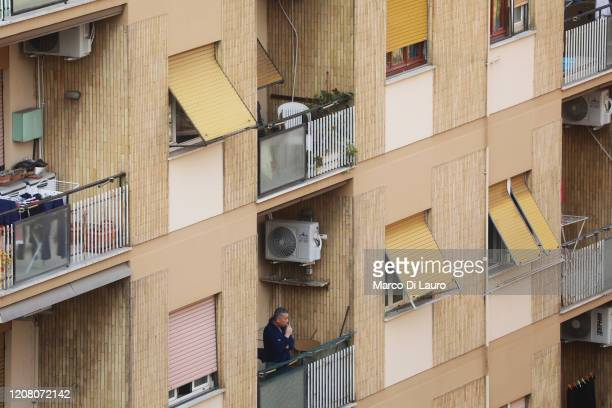 A man stands on his balcony on March 22 2020 in Rome Italy As Italy extends its nationwide lockdown to control the spread of COVID19 its citizens are...