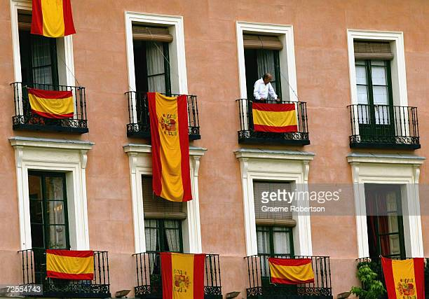A man stands on his balcony surrounded by draped Spanish Flags outside the Almudena cathedral on May 21 2004 in Madrid Spain Spanish Crown Prince...