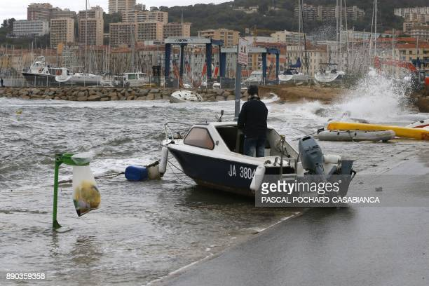 A man stands on his boat pushed onto the dock by waves in Ajaccio on the French Mediterranean Island of Corsica on December 11 2017 The island is on...